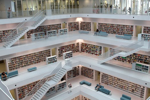 Large open space modern library with white floors and ceiling to floor shelves typical of traditional libraries.