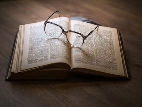 glasses on top of book open to read for young people
